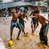 Children play a game of football under the monsoon rains.