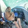 Un homme, assis devant une tente, avec un petit chien sur son épaule.