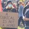 une femme tient une pancarte où il est inscrit : un cubique n'est pas une maison