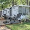 Une roulotte et une balançoire sur un terrain de camping.