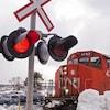 Une locomotive du CN à l'arrêt devant un feu de circulation de voie ferrée à proximité d'un stationnement de voitures.