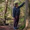 Candace Campo est dans la forêt. Elle regarde et touche un arbre.