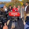 Des candidats libéraux de la région d'Ottawa, dont Steven MacKinnon, Catherine McKenna, Mona Fortier, Marie-France Lalonde et Greg Fergus, derrière un lutrin près de la rivière des Outaouais lors d'un point de presse.