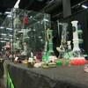 Une passante observe les vaporisateurs de formes et de couleurs différentes sur un des nombreux kiosques au HempFest.