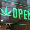 Un panneau annonçant ouvert en anglais avec une feuille de cannabis sur une vitrine de magasin.