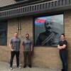 Deux hommes et une femme sont debout devant l'image de Sam Steele à la boutique de cannabis Jimmy's à Cranbrook.