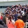 Les joueurs des Cantonniers de Magog ont revêtu le chandail de leur équipe. Ils sont sur le derrière d'un camion. Un des joueurs tient dans ses mains un trophée. Une caméra les filme.