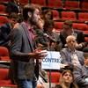 Une jeune homme parle au micro dans un amphithéâtre.