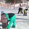 Des enfants en habits de neige dessinent sur la neige avec des jets de couleurs.