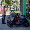 Un homme observe des scooters électriques devant la boutique de Motorino Electric, à Vancouver.