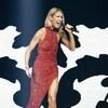 Céline Dion chante sur scène dans une robe rouge.
