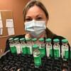 Une infirmière tient un plateau contenant une dizaine de fioles de vaccin.