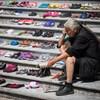 Un homme en deuil assis près de chaussures symbolisant des enfants autochtones disparus.