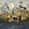 Un homme escalade des rochers au bord de la mer.