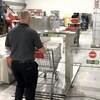 Un homme pousse un panier d'épicerie dans le robot désinfectant.