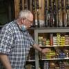 Fernand Lebrasseur devant un étalage de munitions et de fusils.