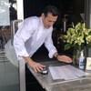 Le chef range des menus une une clochette de restaurant sur la table qui est à moitié à l'intérieur, à moitié à l'extérieur.