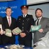 Stephen Tanner aux côtés de policiers à une conférence de presse qui montrent des armes et de l'argent saisis.