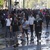 Des protestataires masquées marchent dans les rues de la capitale.