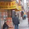 Une rue avec des magasins chinois et des gens qui marchent.