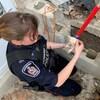 Une policière avec un tout petit chiot dans ses mains près d'un bloc de béton avec des trous.