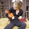 Stef Lowey tient une poule rousse et un œuf.