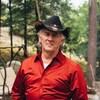 Un homme est debout dans la forêt. Il porte un chapeau et une chemise rouge.