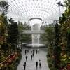 La chute intérieure, bordée de végétation, s'écoule au centre d'un dôme de verre.