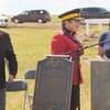 Plusieurs personnes sont debout près d'une plaque qui reconnaît le terrain du cimetière de l'École industrielle autochtone de Regina comme site patrimonial provincial.