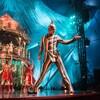 Un artiste de cirque déguisé sur scène tend la main. Derrière lui, on voit un carrousel entouré par plusieurs personnes.