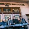 Six personnes souriantes tiennent une banderole sur laquelle il est écrit Hôtel Clarendon. Une des personnes tient aussi des ciseaux et coupe la banderole.