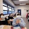 Les jeunes assis et assises à leur pupitre dans une salle de classe montrent le livre de manière à cacher leur visage.