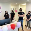 Les employés de la clinique dentaire Northern Smile prennent la pose avec un masque à l'intérieur de la réception de la clinique