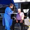 Une infirmière fait passer un test de dépistage à un homme, devant le véhicule de la clinique mobile.