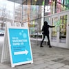 Une personne ouvre la porte de l'entrée d'une clinique de vaccination à Montréal.