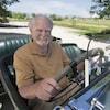 Clive Cussler, au volant d'une voiture, porte une barbe blanche.