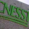 Plan rapproché sur le logo ornant le siège social de la CNESST à Québec. Les lettres C-N-E-S-S-T sont peintes en vert.