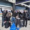 Les quatre musiciens et la directrice de tournée pointent le ciel, entourés de leur bagages.