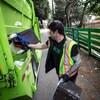 Un éboueur verse le contenu d'une poubelle dans un camion à ordures.