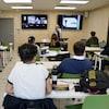 Des élèves sont assis en classe. Une enseignante est devant la classe.