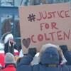 Un manifestant de dos tient une pancarte sur laquelle il est écrit « justice pour Colten ».