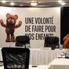 Un ourson en peluche à côté d'un affiche de la Commission Laurent.
