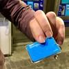 Une main tenant une petite carte bleue.