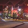 Des pompiers devant deux camions d'incendie arrosent les flammes de la maison.