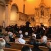 Un orchestre joue dans une église devant des spectateurs.
