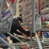 Un homme est accroupi devant une étagère de supermarché. Devant lui se trouvent deux paniers remplis de denrées dont de la sauce tomate et des couches.
