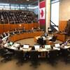 Une table ronde où siègent une vingtaine de personnes, et une tribune pour le public bondée.