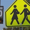 Deux panneaux, un illuminé montrant la vitesse permise et l'autre jaune représentant deux enfants qui marchent.