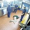 Un homme couché sur le sol menotté dans un poste de police, avec trois policiers debout autour de lui.