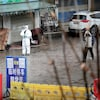 Un homme habillé d'un habit de protection contre la contamination se tient debout dans le marché fermé.